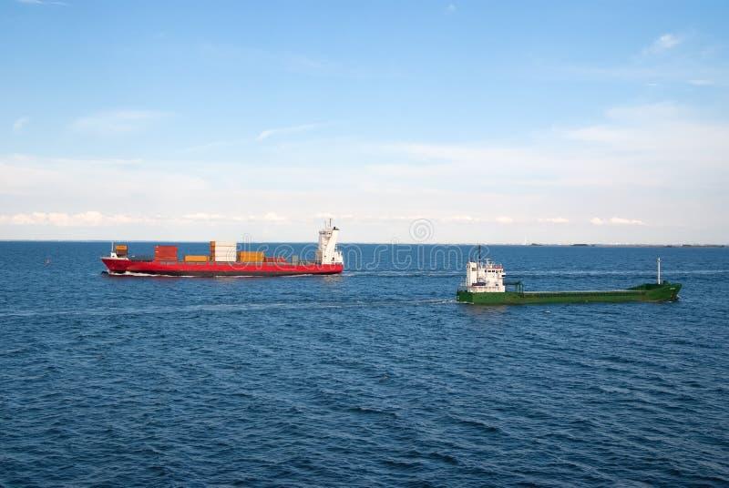 Las gabarras envían los contenedores para mercancías en el mar en Copenhague, Dinamarca Los buques de carga flotan en el mar azul fotografía de archivo libre de regalías