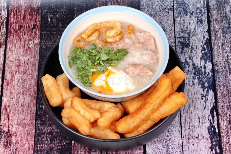 Las gachas de avena del arroz del ` s del cerdo sirvieron con el palillo frito de la pasta fotografía de archivo libre de regalías