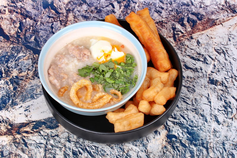 Las gachas de avena del arroz del ` s del cerdo sirvieron con el palillo frito de la pasta fotos de archivo
