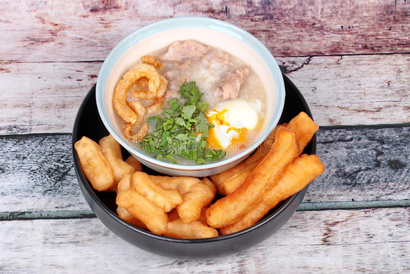Las gachas de avena del arroz del ` s del cerdo sirvieron con el palillo frito de la pasta imagenes de archivo