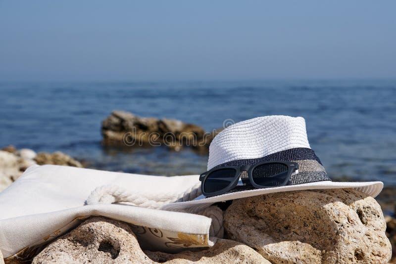 Las gafas de sol con un sombrero y una playa empaquetan foto de archivo libre de regalías