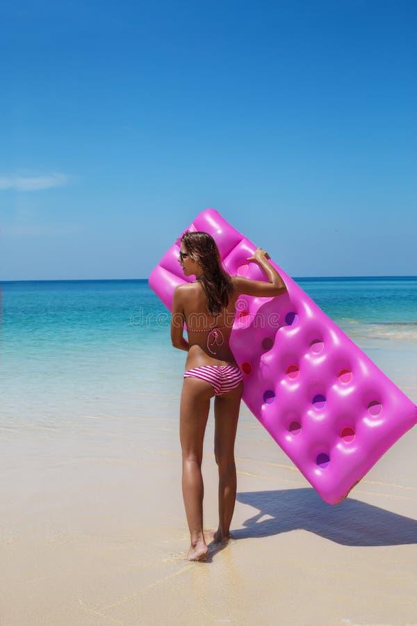 Las gafas de sol morenas de la mujer toman el sol con el colchón de aire en la playa tropical fotos de archivo libres de regalías