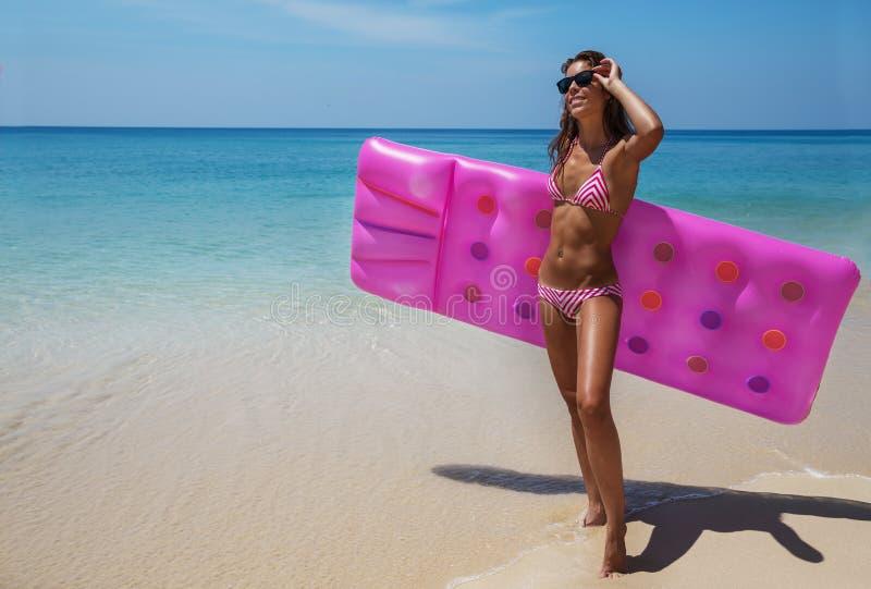 Las gafas de sol morenas de la mujer toman el sol con el colchón de aire en la playa tropical imagenes de archivo