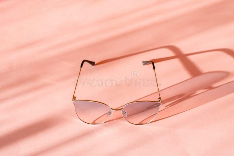 Las gafas de sol rosadas de las mujeres con el marco metálico echaron una sombra en la superficie rosada fotos de archivo libres de regalías