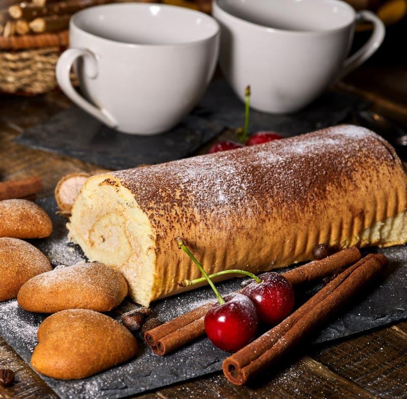 Las galletas de harina de avena, rodaron la torta en soporte de la torta de la grada con la cereza imagen de archivo libre de regalías