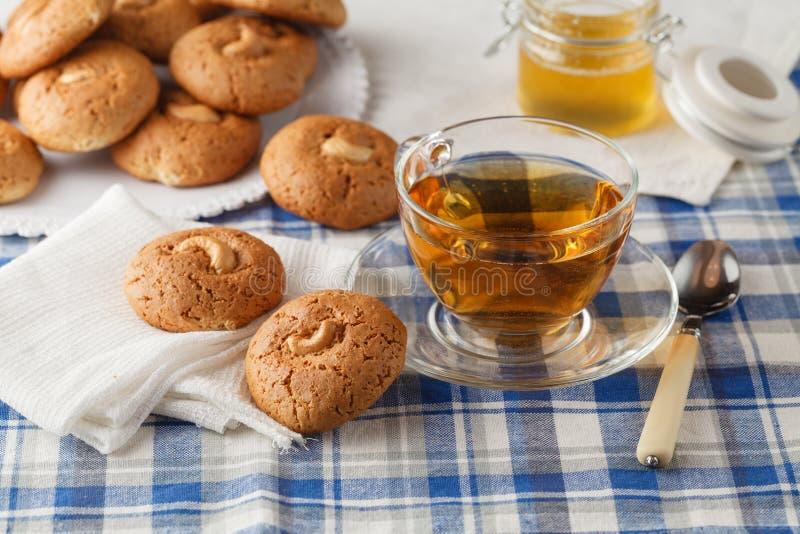 Las galletas de harina de avena con la nuez, tarro con la miel en servilleta en marrón cortejan fotos de archivo