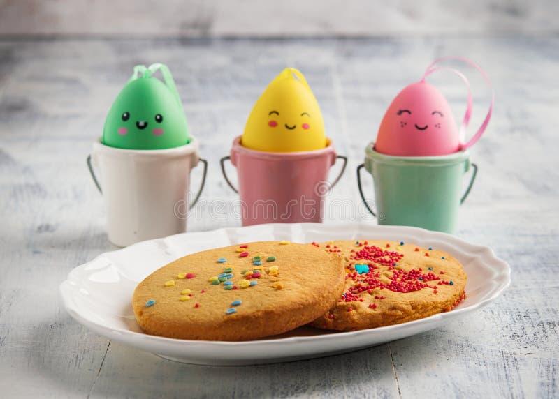 Las galletas de la primavera de Pascua adornadas con asperjan en el fondo rústico blanco Concepto feliz de Pascua imagen de archivo