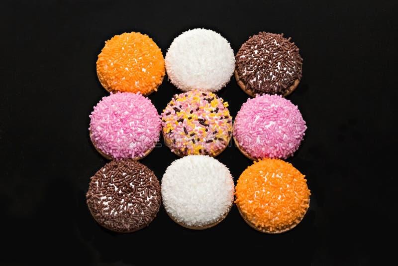 Las galletas de las melcochas con el azúcar coloreado asperjan foto de archivo libre de regalías