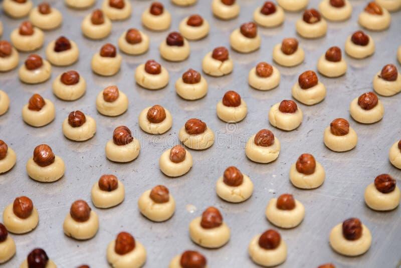 Las galletas de torta dulce del dmall del primer en las bolas del formround en el molde para el horno con el papel, con las nuece imagen de archivo