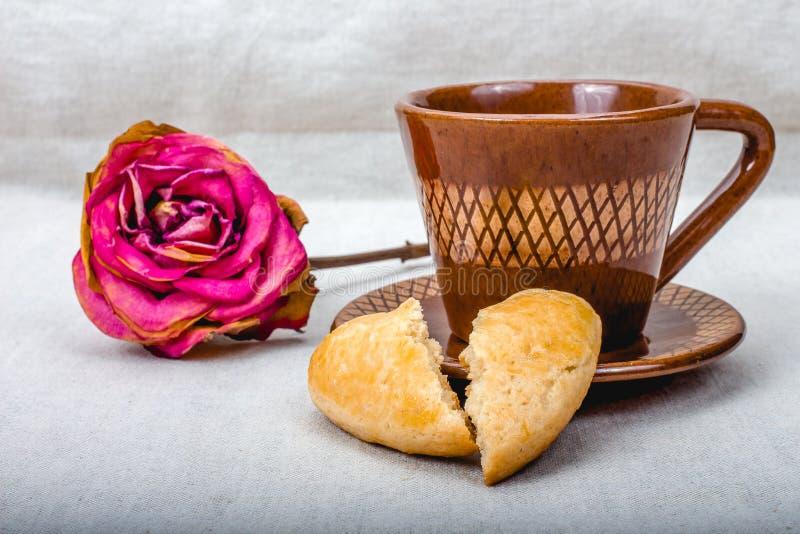 Las galletas del corazón quebrado, taza de café, secada subieron foto de archivo