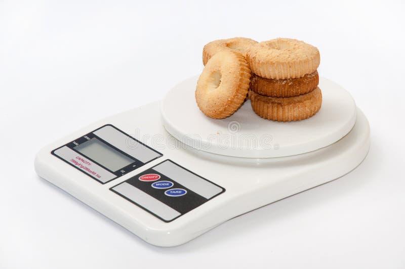 Las galletas del té arreglaron en una escala digital medir fotos de archivo