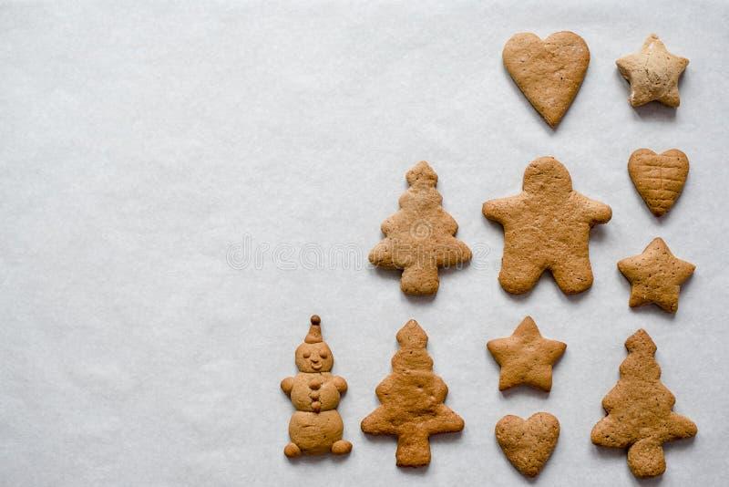 Las galletas en el muñeco de nieve, árboles de navidad, corazones, estrellas del pan de jengibre de la Navidad están en un fondo  imagen de archivo libre de regalías