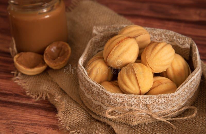 Las galletas hechas en casa formaron nueces con el milkt condensado hervido crema en la tabla de madera fotografía de archivo libre de regalías