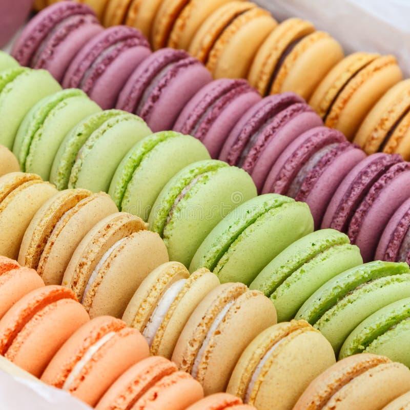 Las galletas hechas a mano sabrosas multicoloras redondas se apilan en fila en una caja foto de archivo