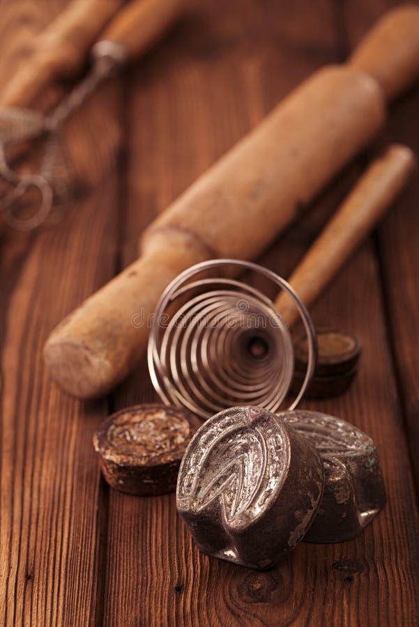 Las galletas retras de la cocina moldean las herramientas de los utensilios en Tabla I de madera vieja imagenes de archivo