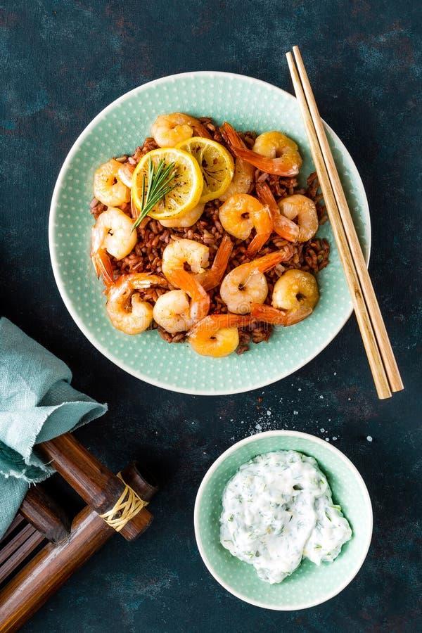 Las gambas asaron en parrilla e hirvieron el arroz moreno en la placa Camarones asados a la parrilla, gambas con arroz Mariscos C foto de archivo