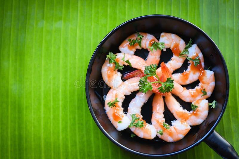Las gambas cocinadas de los camarones de la placa de los mariscos adornan la cacerola con el fondo de la hoja del pl?tano de las  foto de archivo libre de regalías