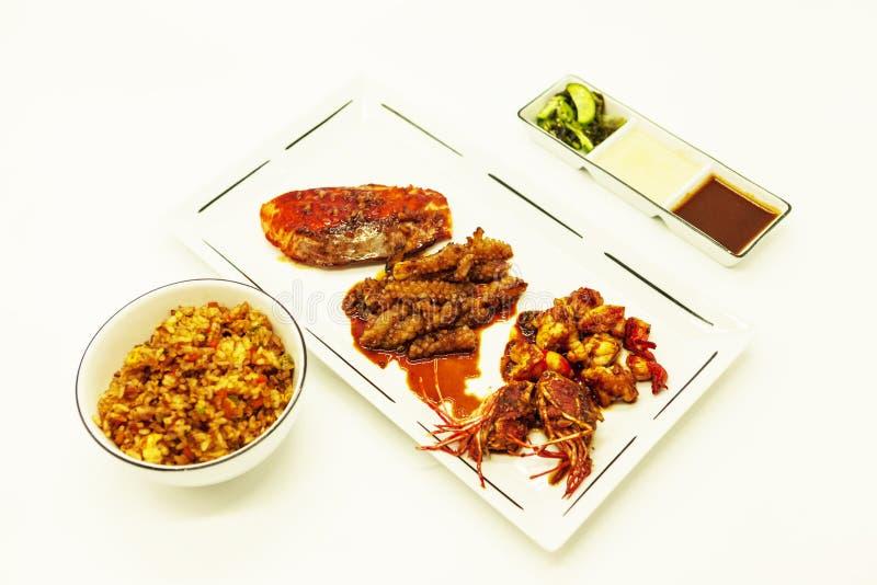 Las gambas y el pulpo fritos del tigre en un estilo chino asaron a la parrilla la barbacoa en un aceite picante con arroz frito y fotos de archivo