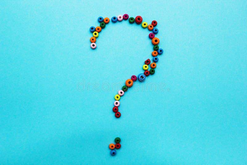 Las gotas de los niños multicolores, dispersadas en un fondo azul, signo de interrogación fotos de archivo