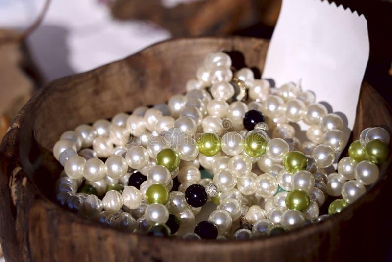 Las gotas de las perlas negras, blancas y verdes mienten en un florero de madera fotografía de archivo