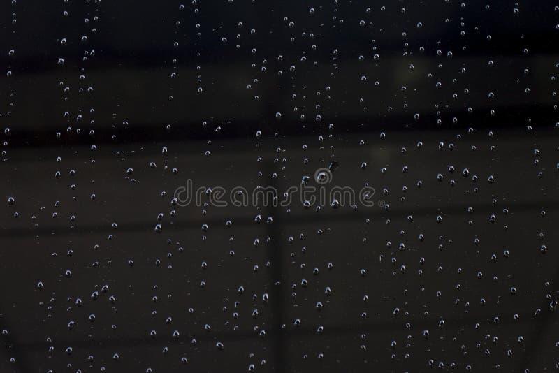 Las gotitas de agua fluyen sobre el vidrio negro foto de archivo