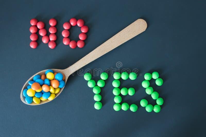 Las grageas coloreadas de los caramelos mienten en una cuchara de madera, en los lados de la palabra sí y no, en un fondo negro imagenes de archivo
