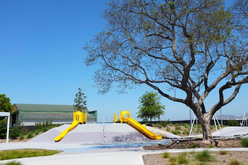 Las grandes diapositivas de las características del área del juego de niños del parque del Condado de Orange, oscilaciones, gimna imagen de archivo