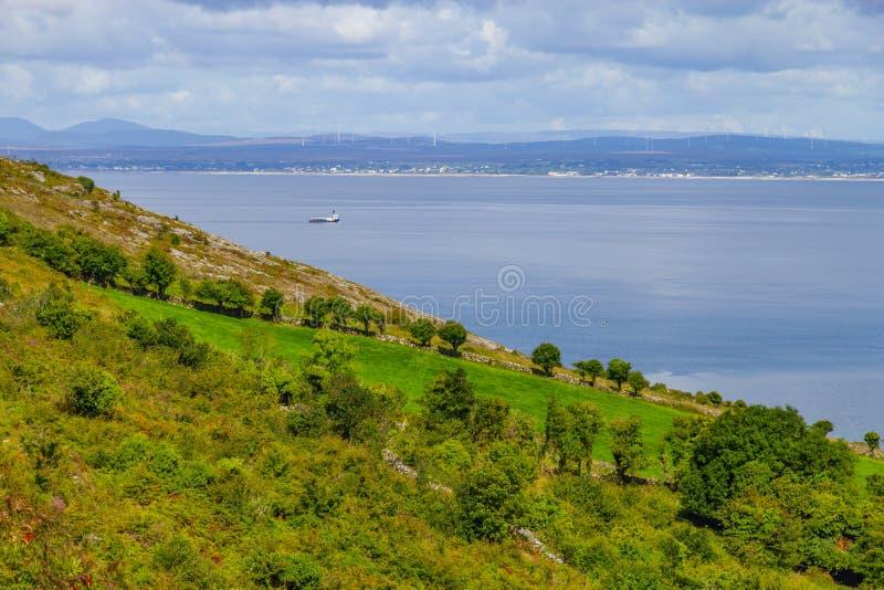 Las granjas de la manera de Burren se arrastran con la bahía y el barco de Galway en fondo fotografía de archivo
