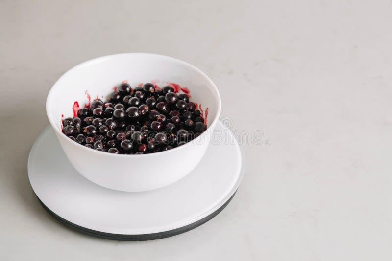 Las grosellas negras en un cuenco de cerámica blanco están en una escala de la cocina Visi?n superior Pasas maduras y sabrosas en imágenes de archivo libres de regalías