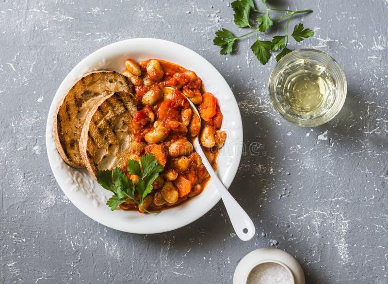 Las habas de Lima cocidas picantes en salsa de tomate y ciabatta tuestan en un fondo gris, visión superior Almuerzo vegetariano d imágenes de archivo libres de regalías