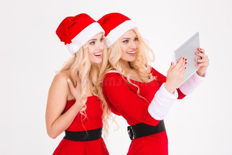 Las hermanas atractivas felices hermanan la fabricación del selfie usando la tableta fotografía de archivo libre de regalías