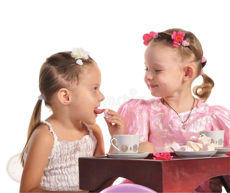 Las hermanas bonitas de los gemelos hacen té aislar imágenes de archivo libres de regalías