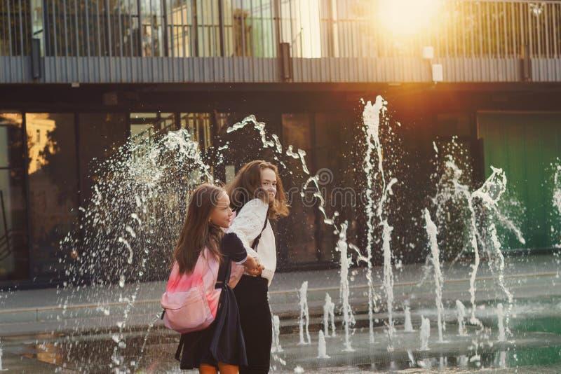 Las hermanas caminan por la fuente de la ciudad fotos de archivo libres de regalías