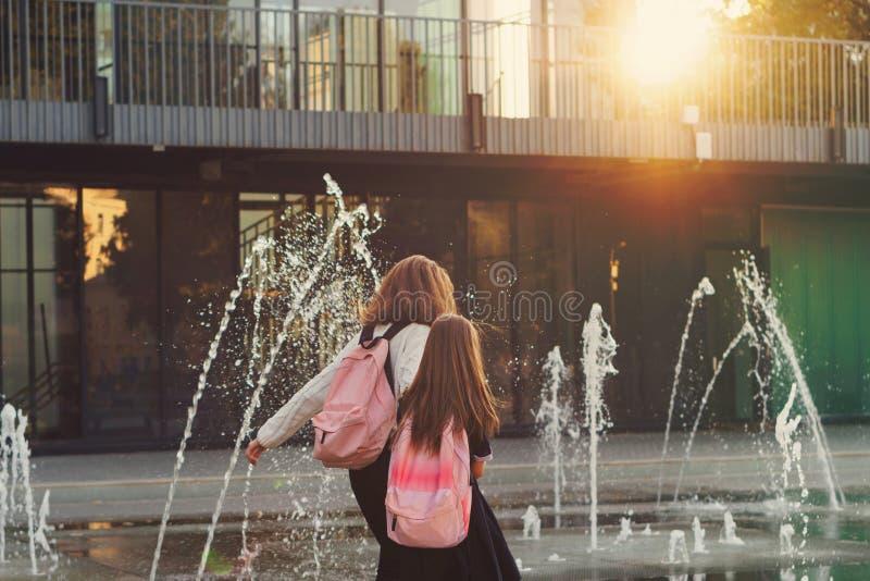 Las hermanas caminan por la fuente de la ciudad fotografía de archivo