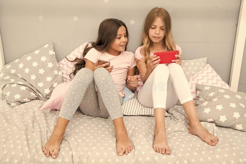 Las hermanas de las muchachas llevan el pijama ocupado con smartphones Los ni?os en pijama obran rec?procamente con smartphones U imágenes de archivo libres de regalías