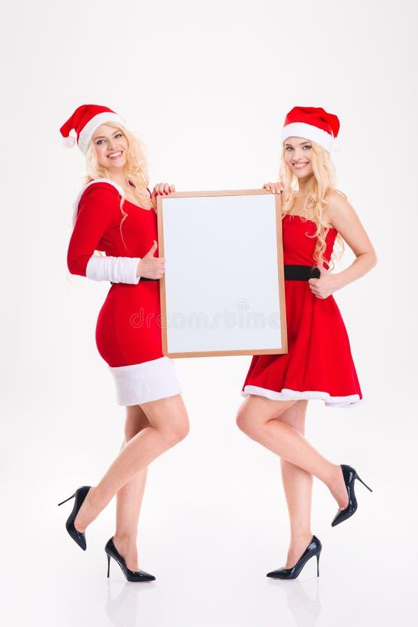 Las hermanas jovenes encantadoras hermanan con el tablero en blanco que muestra los pulgares para arriba imagen de archivo libre de regalías