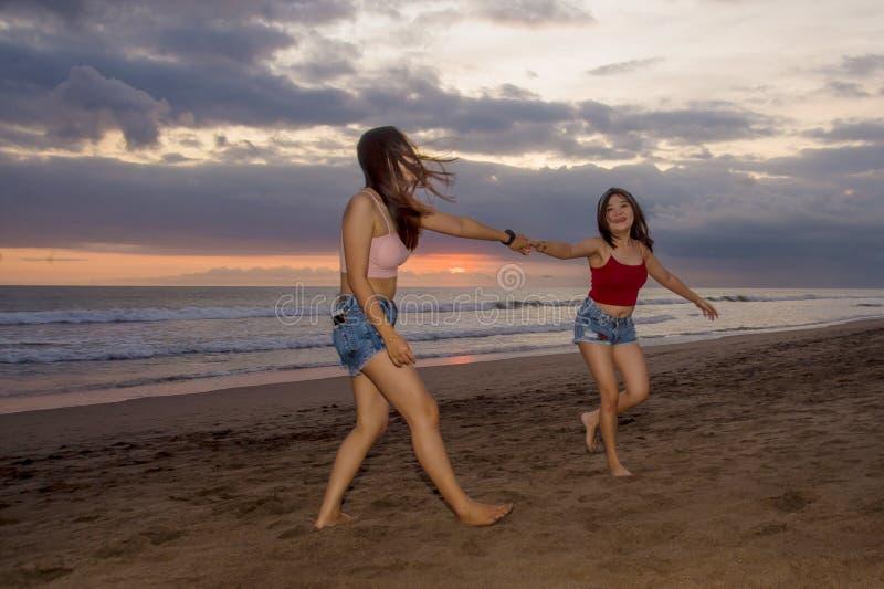 Las hermanas jovenes felices o la muchacha china asiática en la playa de la puesta del sol con su mejor amigo que se divierte que imagen de archivo libre de regalías