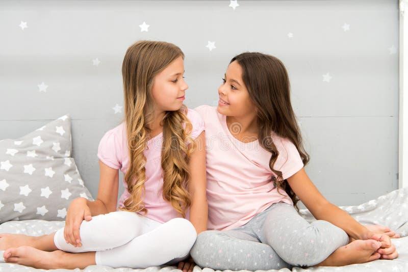 Las hermanas o los mejores amigos pasan el tiempo junto en dormitorio Muchachas que se divierten junto Ocio de niña Amigos de las foto de archivo