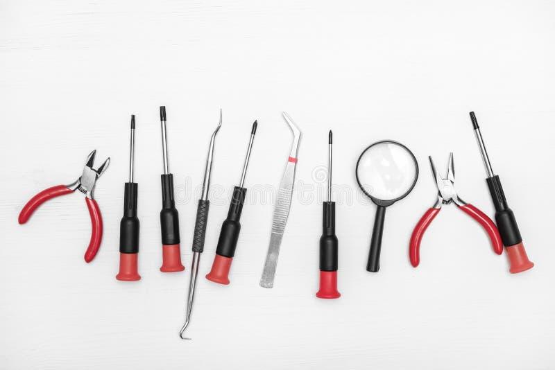 Las herramientas de la reparación de la electrónica son en fila en el centro fondo blanco alineado fotografía de archivo libre de regalías