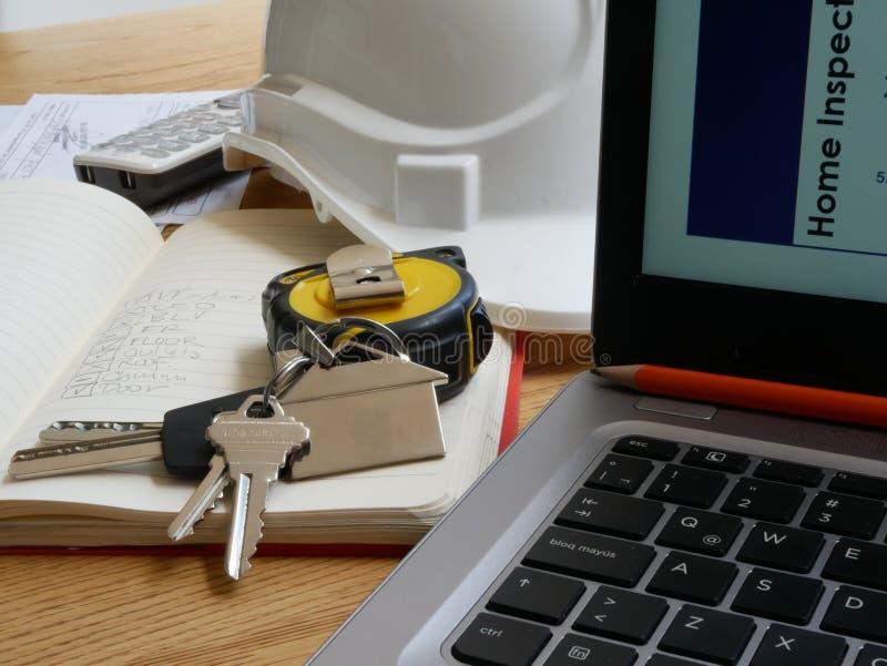 Las herramientas de un inspector usado para llenar un informe de inspección casero de la puerta de la cinta métrica del casco de  fotos de archivo