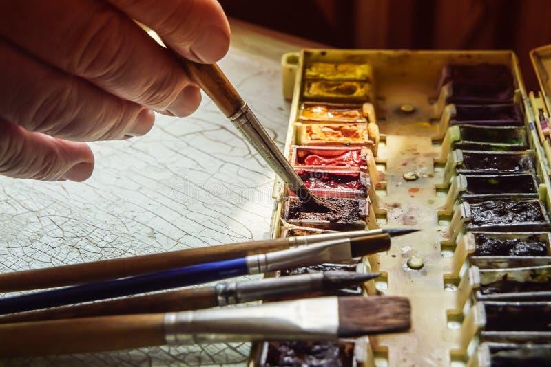Las herramientas del artista, acuarela profesional pintan en una caja, los cepillos del artista y los cepillos en una tabla vieja fotos de archivo