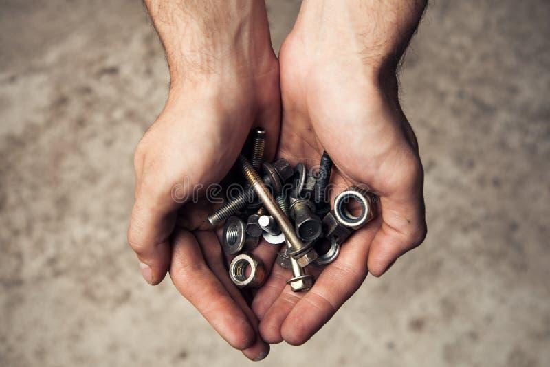 Las herramientas oxidadas del hierro empernan y los tornillos adentro sirven las manos imagen de archivo