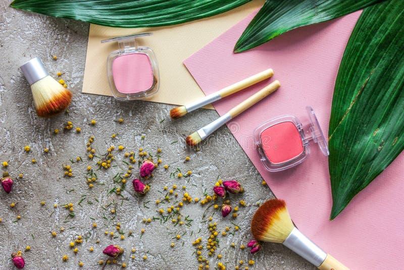 Las herramientas para componen y los cosméticos con los cepillos en modelo de piedra gris de la opinión superior del fondo imágenes de archivo libres de regalías