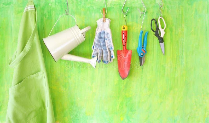 Las herramientas que cultivan un huerto, regadera, scissor, traspalan, delantal, copia libre foto de archivo