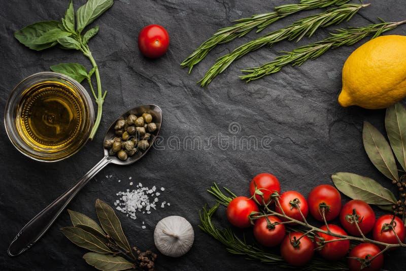 Las hierbas se mezclan con los tomates, el limón y el aceite de oliva en la tabla de piedra negra imagen de archivo