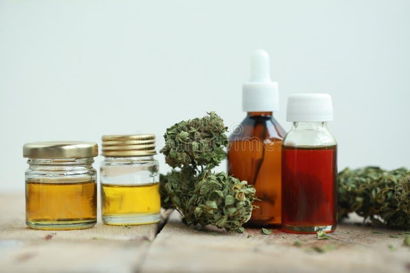 Las hojas del verde de la medicina alternativa de cáñamos medicinales con el extracto engrasan en una tabla de madera imagenes de archivo