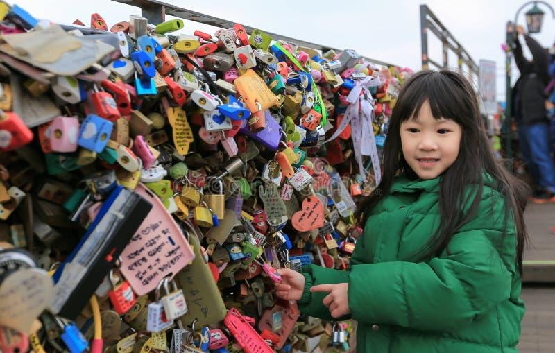 Las imágenes asiáticas de la niña con las llaves cerradas, los candados del amor y las llaves desean amor para siempre en la torr imágenes de archivo libres de regalías