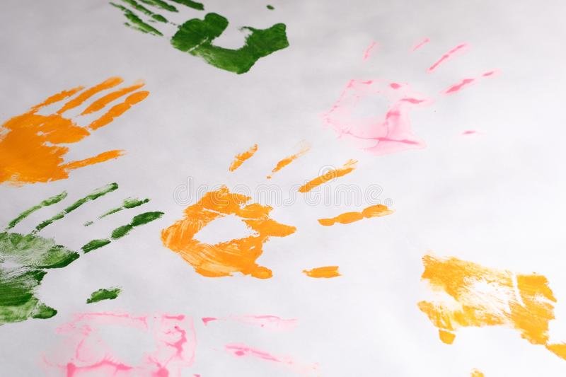 Las impresiones del ` s de los niños dan a la izquierda con diversos colores en el Libro Blanco, creatividad del ` s de los niños fotos de archivo