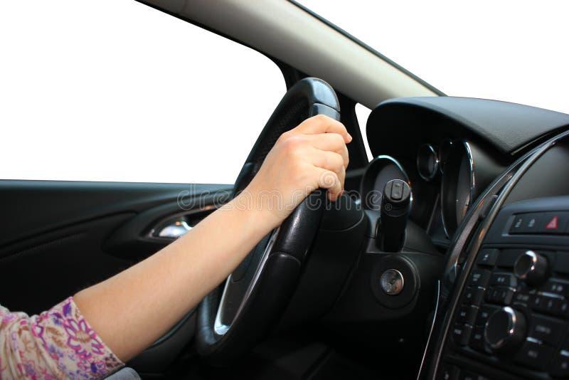 Las impulsiones de la muchacha un coche, sostienen el volante con una mano, fondo blanco aislado fotografía de archivo libre de regalías