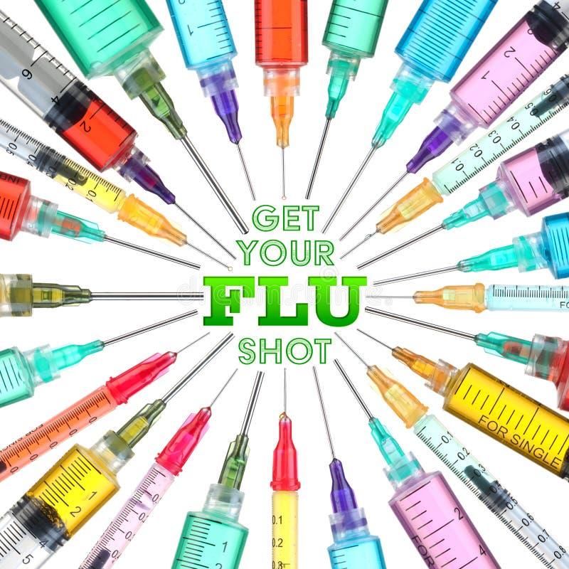 Las jeringuillas brillantes y coloridas - consiga su vacuna CONTRA LA GRIPE imagen de archivo